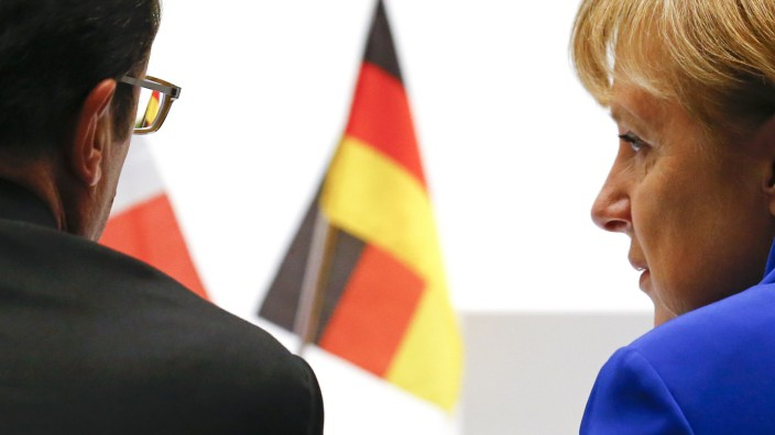 France's President Hollande talks with Germany's Federal Chancellor Merkel during the Asia-Europe Meeting (ASEM) in Milan