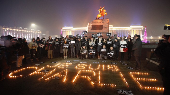 Mongolian journalists pay tribute to the victims of a shooting by gunmen at the offices of French weekly newspaper Charlie Hebdo in Paris, at Genghis Square in Ulan Bator