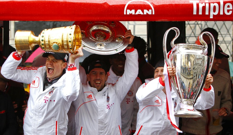 Bayern Munich's Neuer, Ribery and Schweinsteiger holds up trophies as they make their way in a parade to Munich town hall