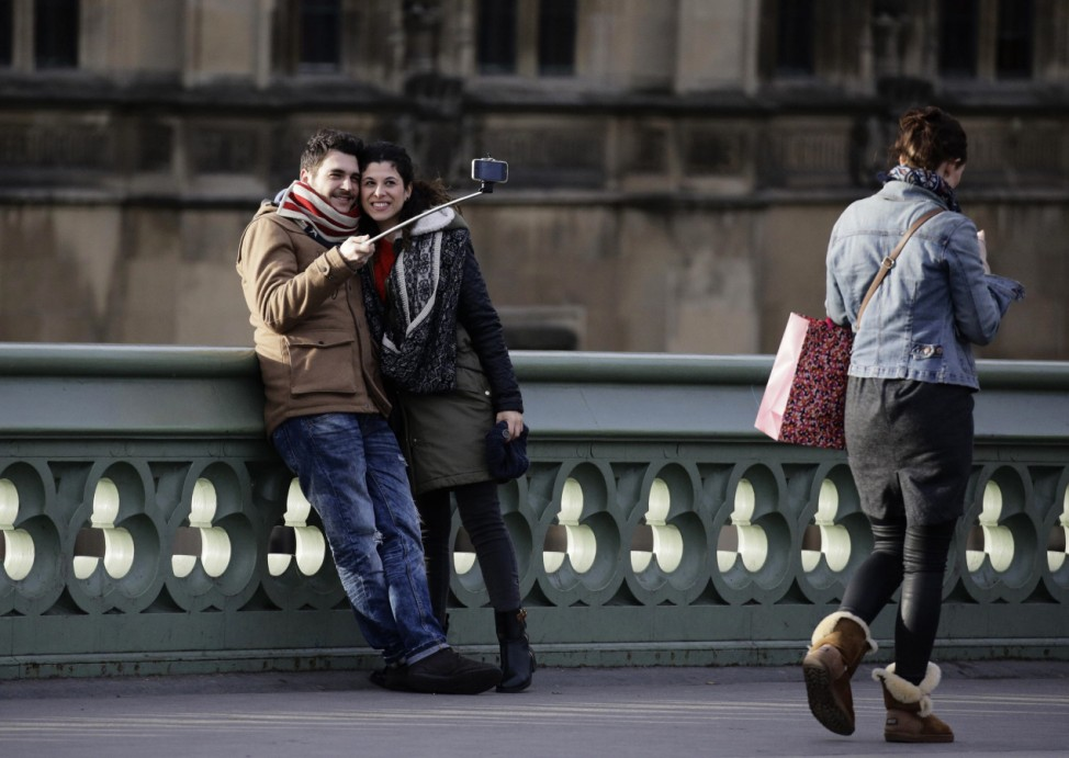 People take a photo using a 'selfie' stick whilst standing on Westminster Bridge in London