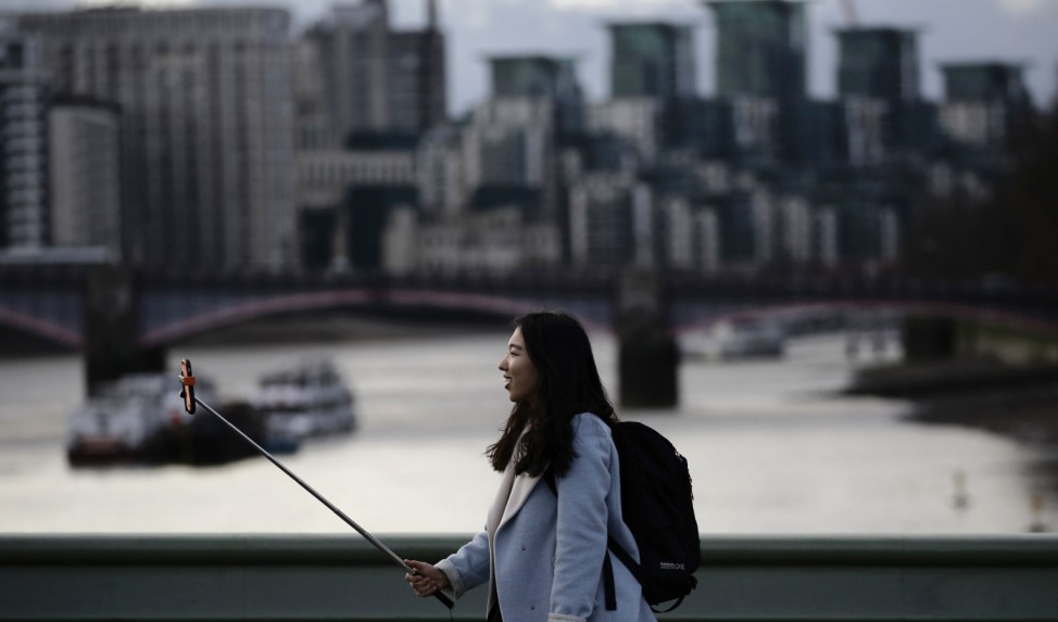 A woman takes a photo using a 'selfie' stick whilst standing on Westminster Bridge in London