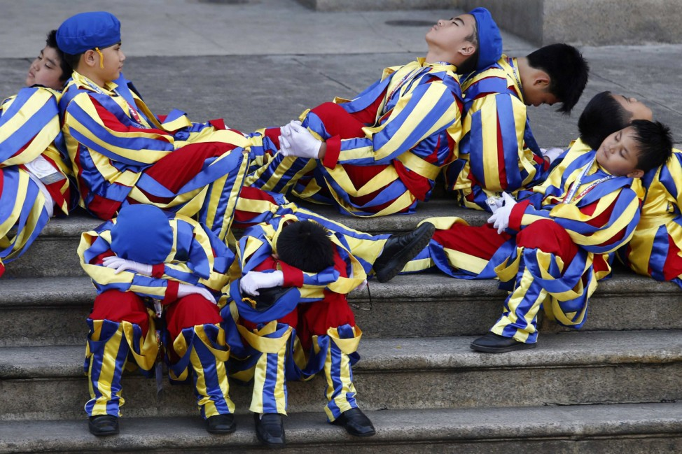Schoolchildren dressed as Swiss Guards rest as they wait for the arrival of Pope Francis outside the Manila Cathedral in Manila
