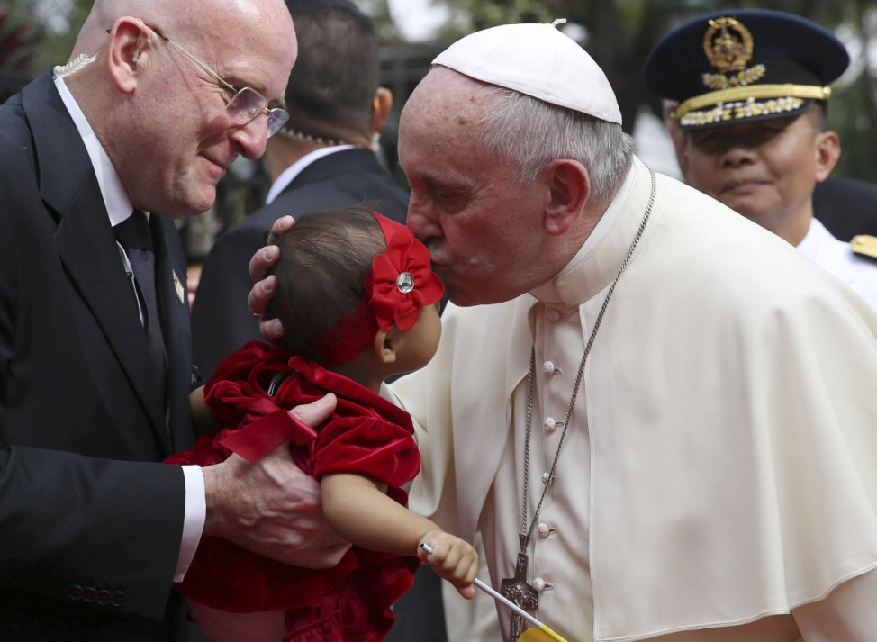 Pope Francis kisses a child at the Malacanang Palace in Manila