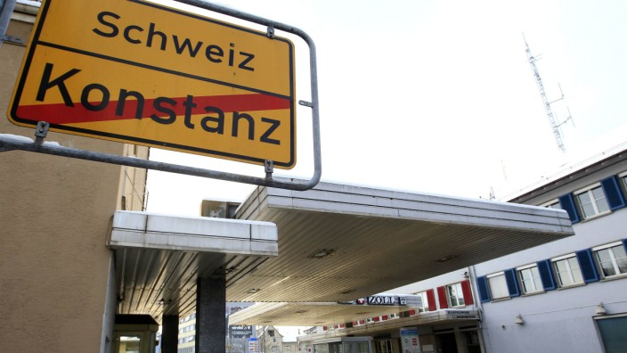 A traffic sign is pictured in front of a border crossing between the German town of Konstanz and the Swiss town of Kreuzlingen