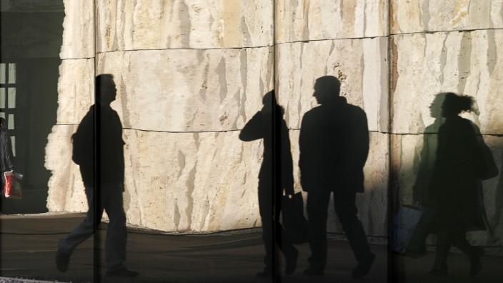 Nach Anschlägen in Paris: Spiegelung von Menschen vor der Außenmauer der jüdischen Synagoge in München. Der Bau am St.-Jakobs-Platz ist gut, aber dezent geschützt.