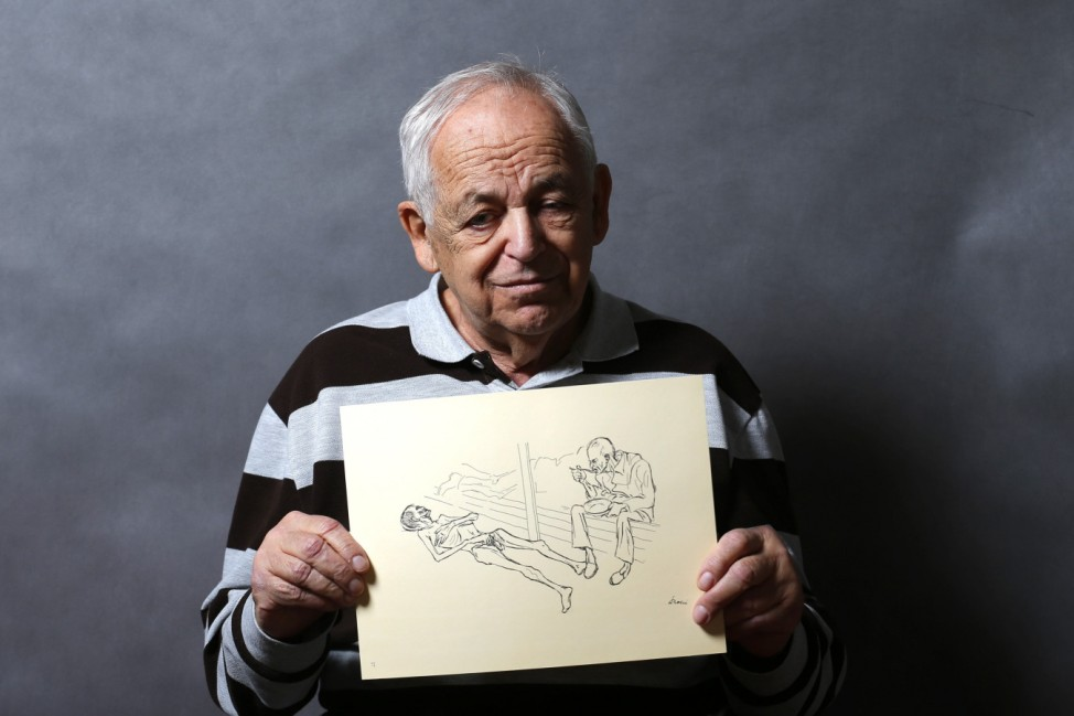 Auschwitz death camp survivor Lajos Erdelyi holds a drawing made by a campmate as he poses for a portrait in Budapest