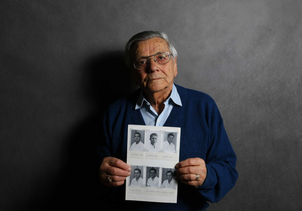Auschwitz death camp survivor Imre Varsanyi holds up a photo of his fellow survivors during World War Two as he poses for a portrait in Budapest