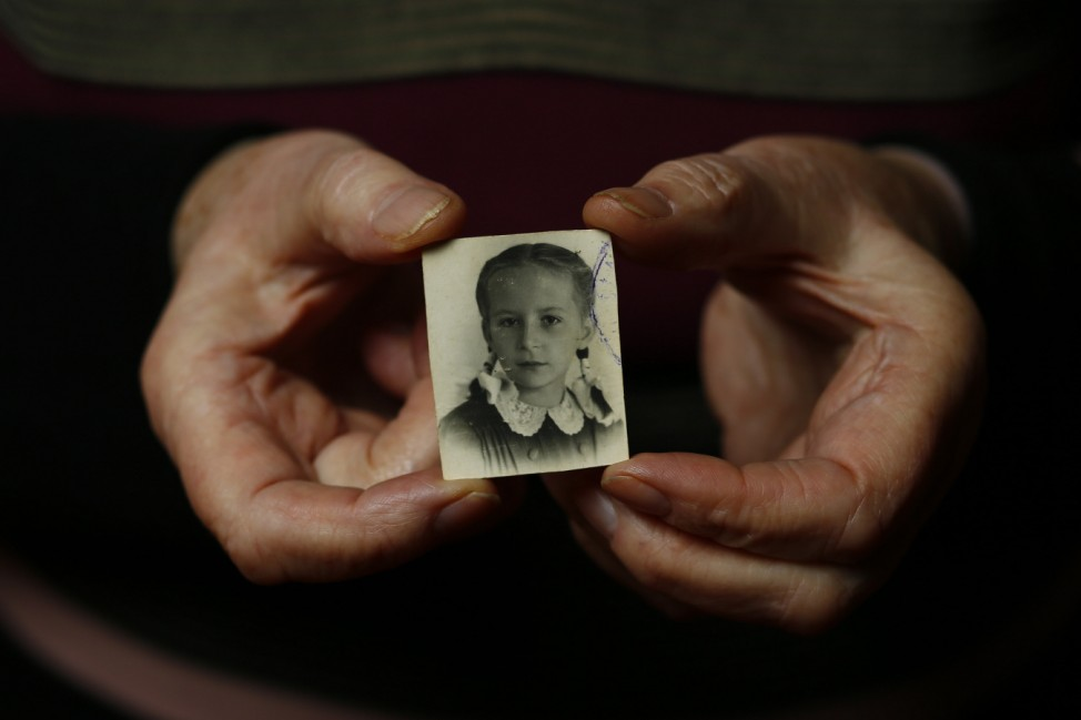 Auschwitz death camp survivor Barbara Doniecka holds up wartime a photo of herself in Warsaw