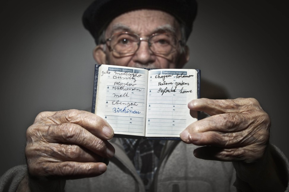 90 year old holocaust survivor Hy Abrams poses for a portrait with a book that he carries with him everyday that documents all the different concentration camps he was held in during the second World War, in the Brooklyn borough of New York