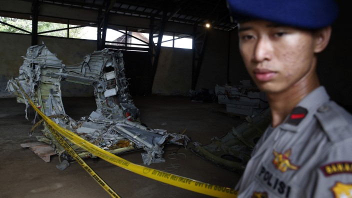 Police officer stands near part of the fuselage of crashed AirAsia Flight QZ8501 inside a storage facility at Kumai port in Pangkalan Bun