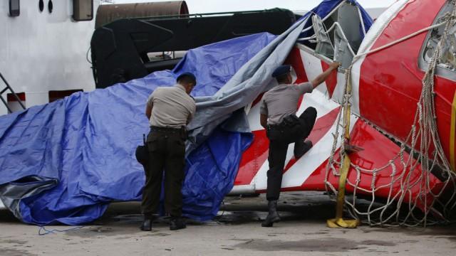 Indonesian police remove tarpaulin from part of the tail of the AirAsia QZ8501 passenger plane in Kumai Port, near Pangkalan Bun