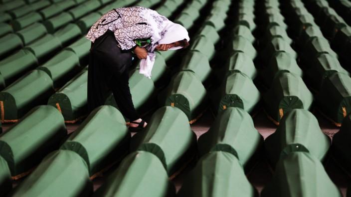 A Bosnian Muslim cries near coffins prepared for a mass burial at the Memorial Center in Potocari, near Srebrenica