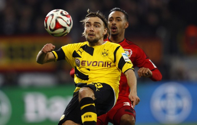 Borussia Dortmund's Schmelzer challenges with Bayer Leverkusen's Bellarabi during their Bundesliga first division soccer match in Leverkusen