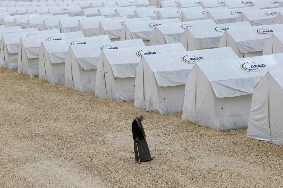 A Kurdish refugee woman from the Syrian town of Kobani walk along tents at a refugee camp in the border town of Suruc
