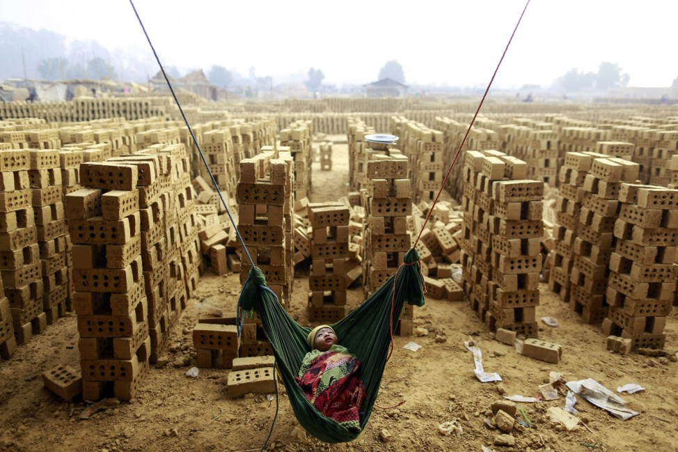 A boy sleeps in a hammock while his mother works at a brick kiln on the outskirts of Yangon
