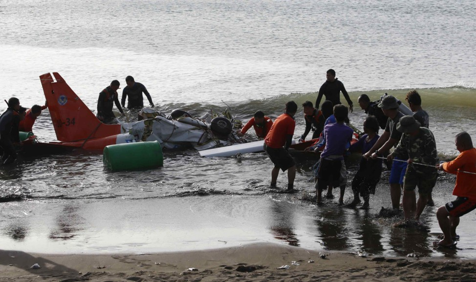 Soldiers and fishermen pull to shore the remains of an ill-fated Philippine Air Force Italian made light aircraft, SIAI-Marchetti SF260, that crashed in the sea off the coast of Nasugbo