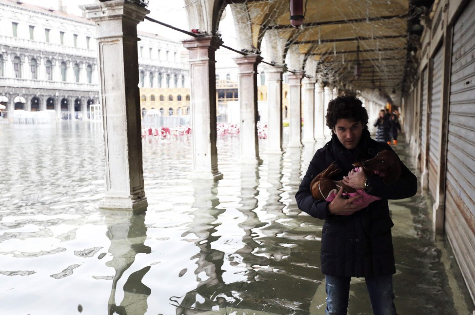 A man carries his dog as he walks through the flooded St. Mark's Square during a period of seasonal high water and on the first day of carnival, in Venice