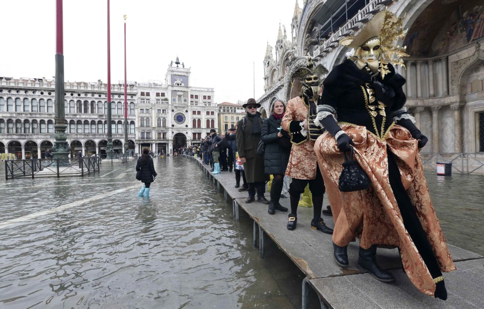 Masked revellers walk on raised platforms above flood waters during a period of seasonal high water and on the first day of carnival, in Venice