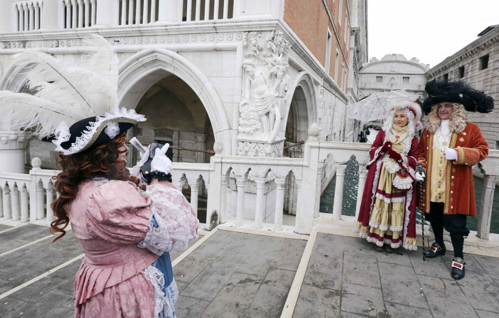 A reveller takes a picture with her mobile phone of friends in front of the Ponte dei Sospiri (Bridge of Sighs) during the first day of the  Venice Carnival