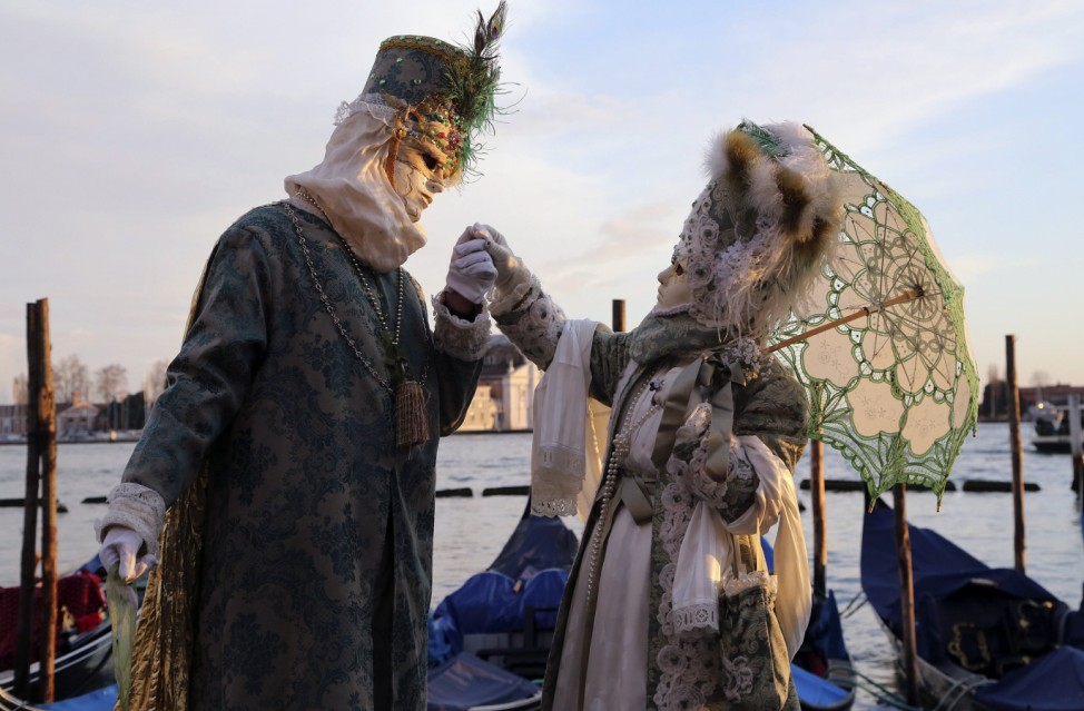 Masked revellers pose in front of St. Mark's square during the first day of carnival in Venice