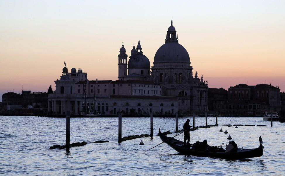 A gondolier rows a gondola in front of 'Punta della Dogana' in the Venetian lagoon