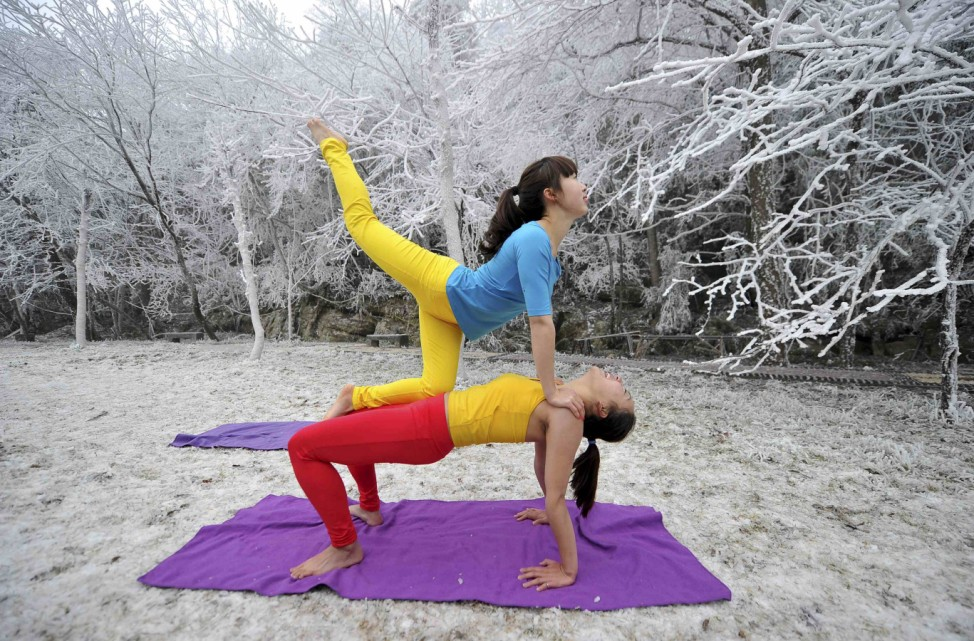 Two women practice yoga next to trees covered in frost at the Tianmen Mountain resort in Zhangjiajie