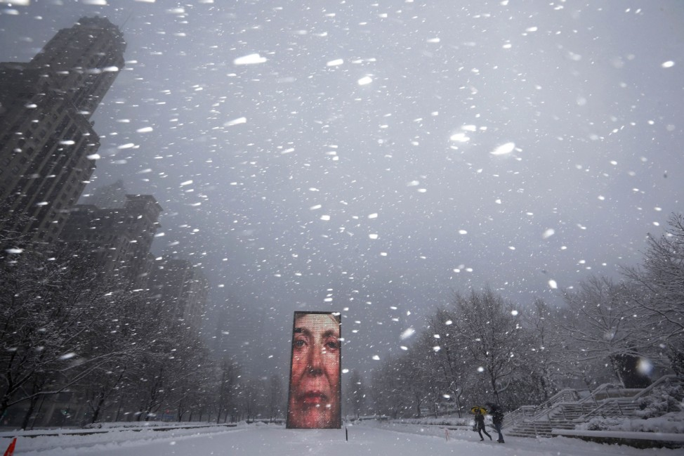Two men walk past the Crown Fountain in blizzard conditions in Chicago