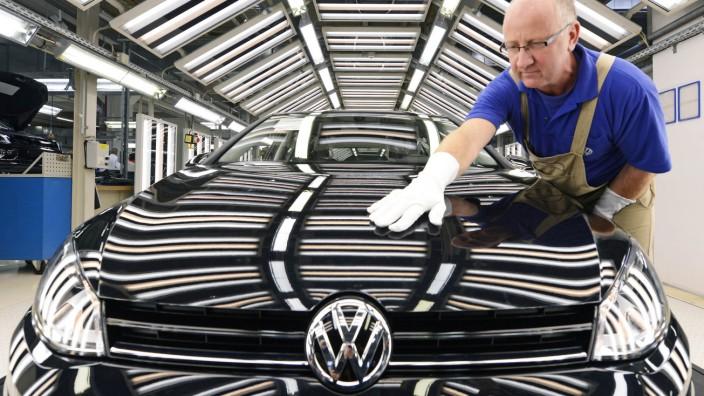 Mitarbeiter von VW poliert den neuen Golf