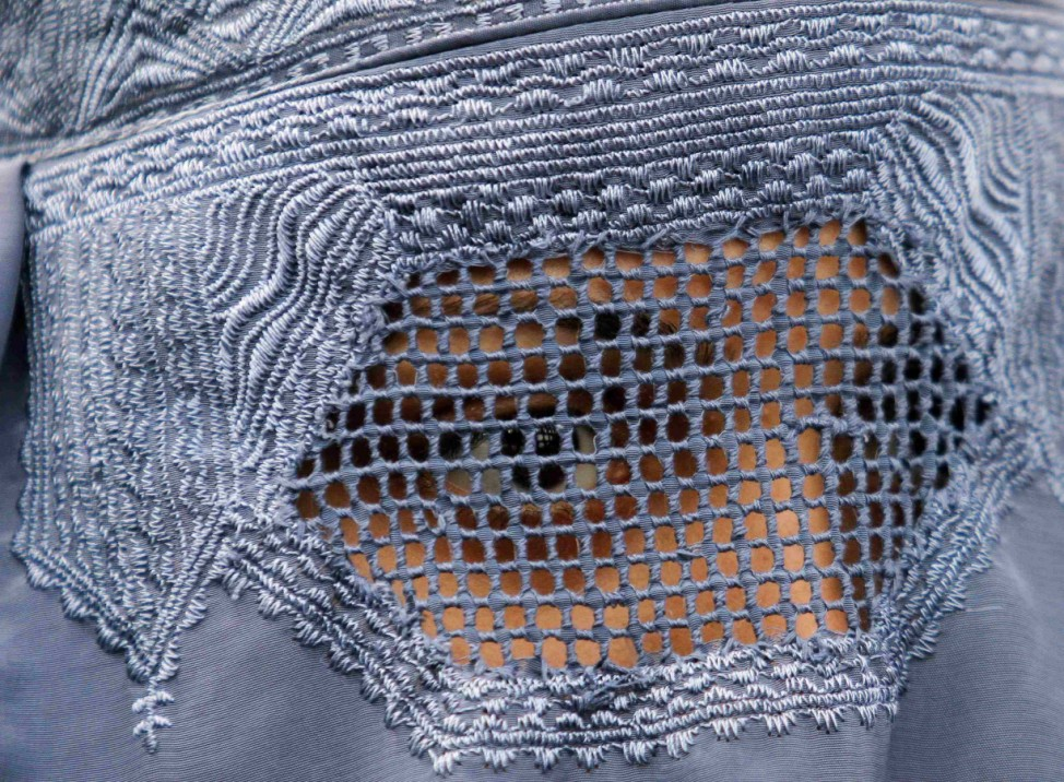 An Afghan refugee woman, clad in a burqa, waits with others to be repatriated to Afghanistan, at the United Nations High Commissioner for Refugees (UNHCR) office on the outskirts of Peshawar