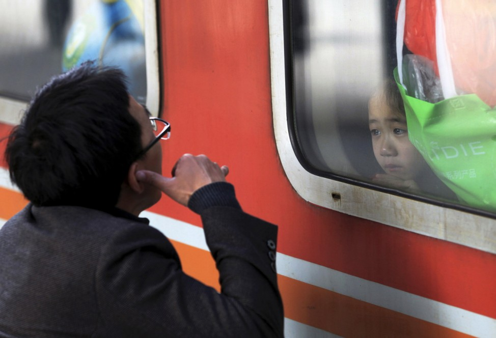 A man gestures to his daughter, who is traveling with her mother to their hometown in Hunan province for the Chinese Lunar New Year, as they bid farewell at a railway station in Shenzhen