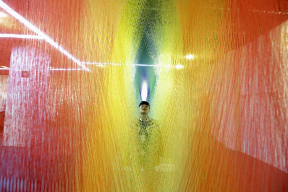 A man looks at a installation made of sock textiles on display at a demonstration hall of the local sock-making industry in Zhuji