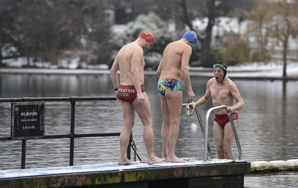 A swimmer reacts as he prepares to swim in the Serpentine lake after snow fall in central London