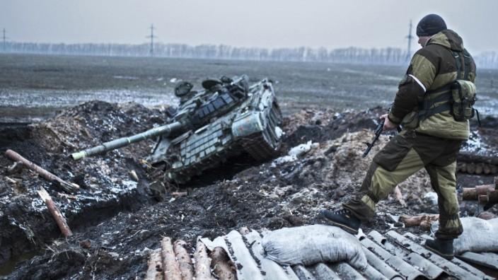 Krieg in der Ukraine: Ein prorussischer Kämpfer bewacht einen Stützpunkt der ukrainischen Armee in der Ostukraine, den die Rebellen erobert haben.