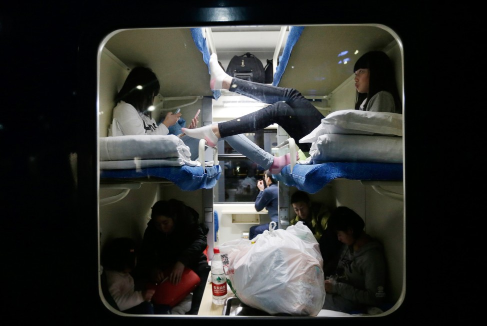 Passengers are seen through the window of a train at Beijing Railway Station