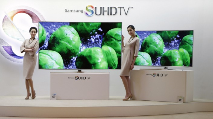 Models pose for photographs next to Samsung Electronics' S'UHD smart TV sets during its launch event in Seoul