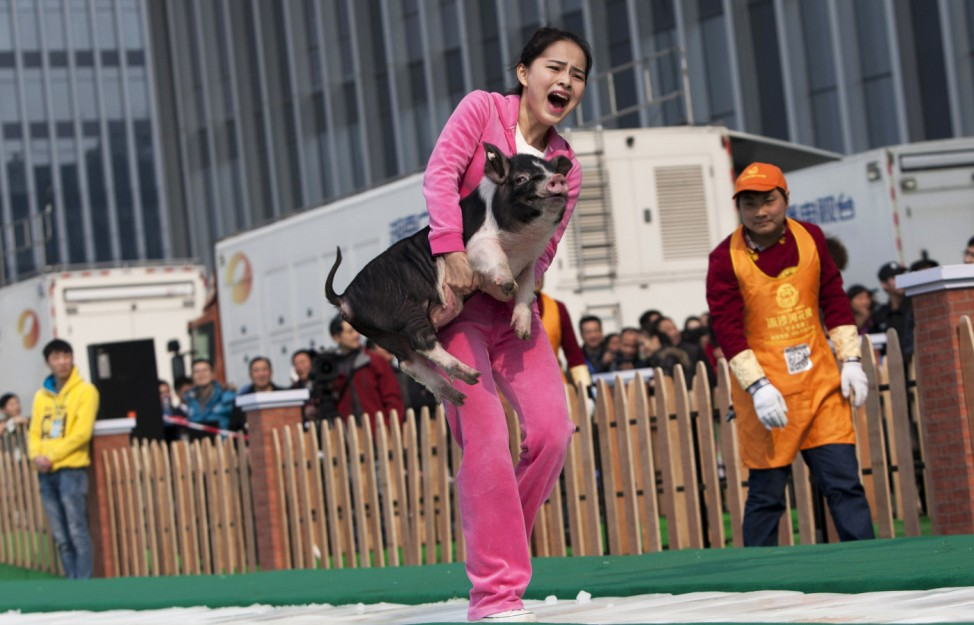 A woman carries a piglet as she runs on ice during a running challenge in Changsha