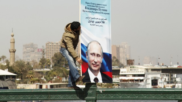 A worker fixes a banner with a picture of Russian President Vladimir Putin along a bridge in central Cairo