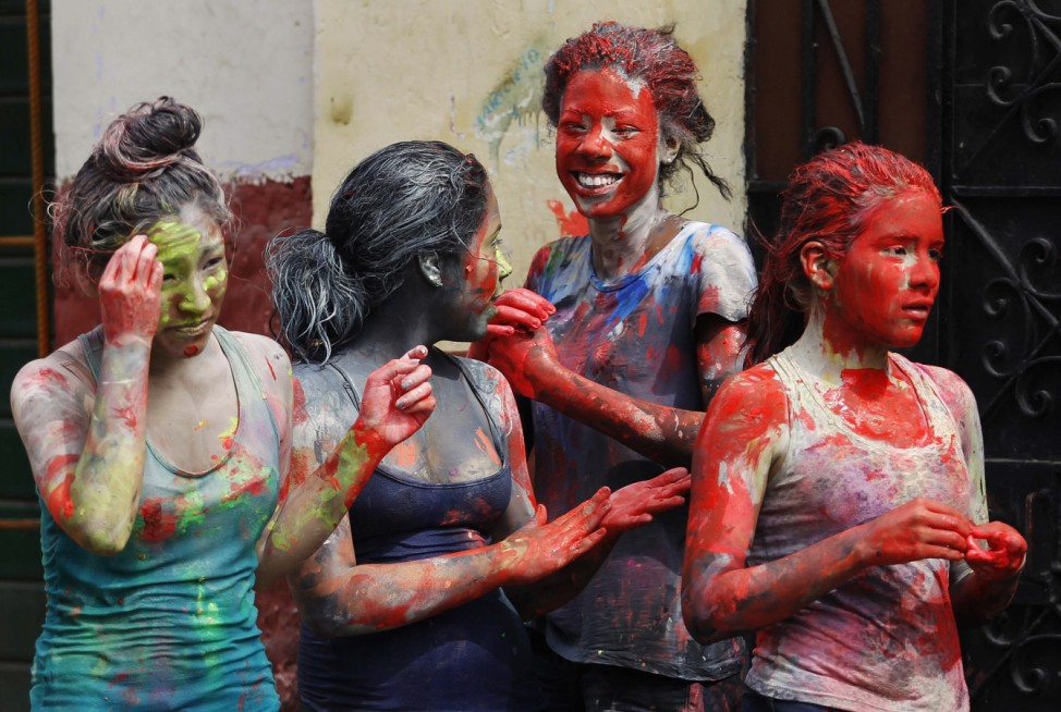 Girls are seen covered with paint after being stained by other children on a street during Carnival celebrations in summer at downtown Lima