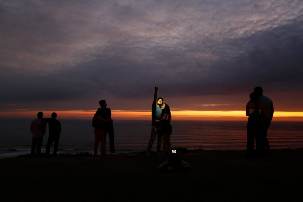 Couple takes a selfie as others observe the sunset at an oceanfront in the neighbourhood of Miraflores in Lima