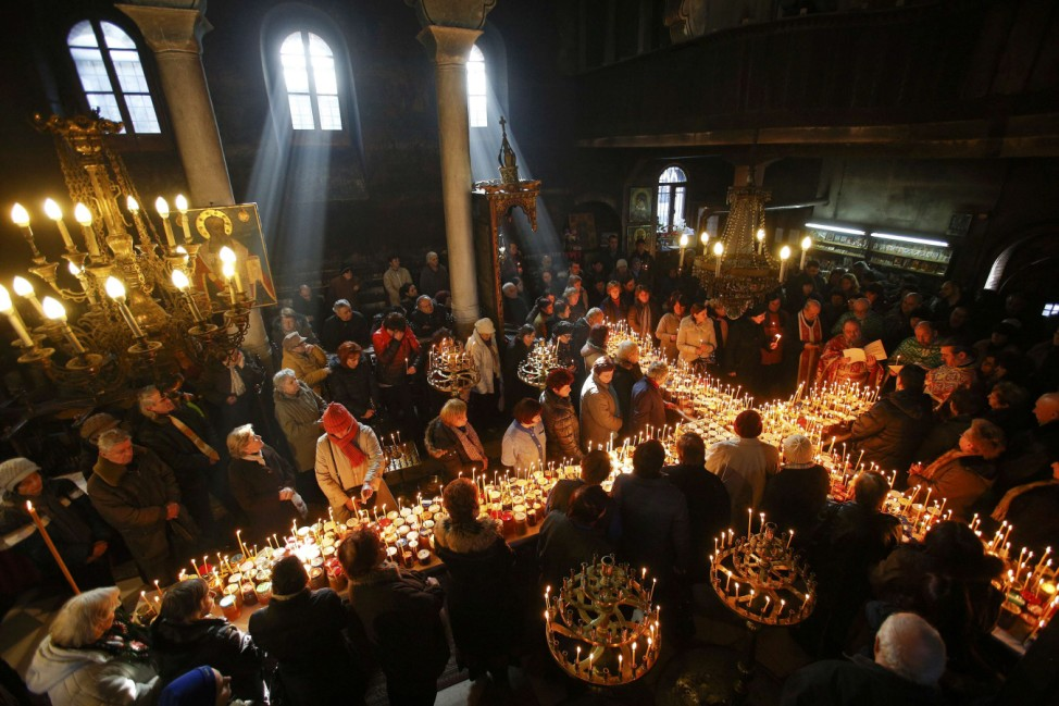 Worshippers gather around candles stuck to jars with honey, during a religious mass in the church of the Presentation of the Blessed Virgin in the city of Blagoevgrad
