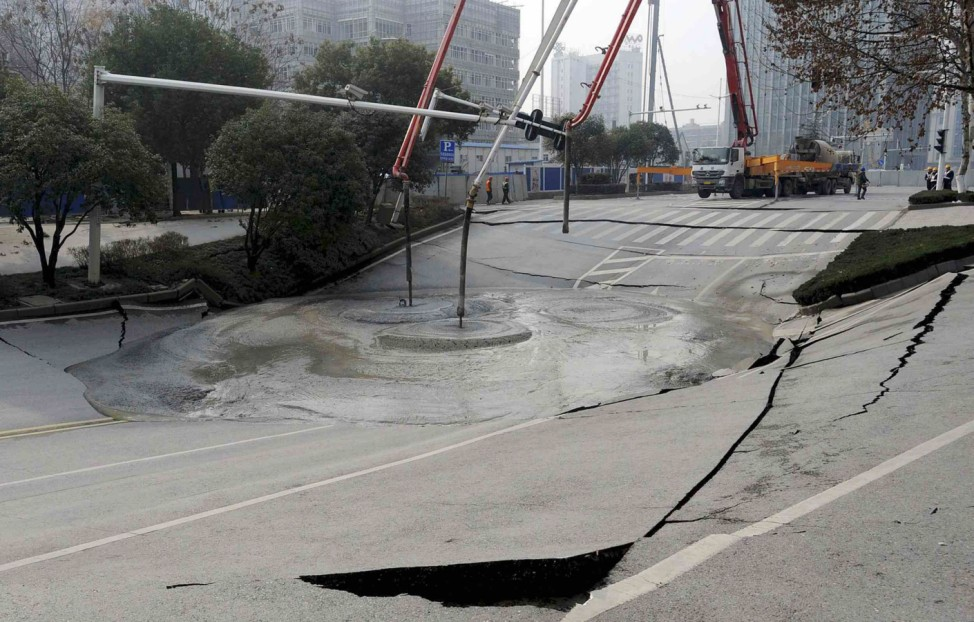 Workers use cement to fill in part of a road that caved in, in Wuhan