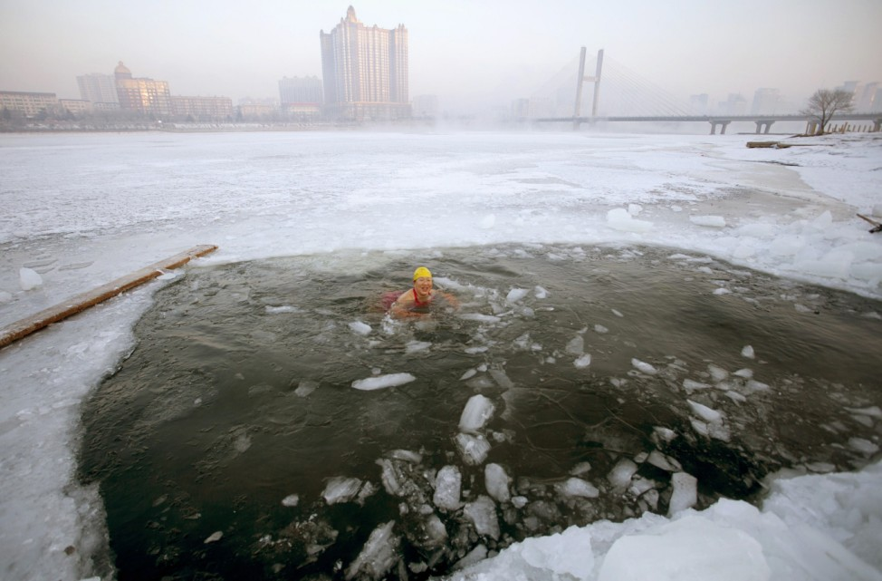 A winter swimmer swims in icy waters after breaking the ice of the frozen Songhua River, in Jilin