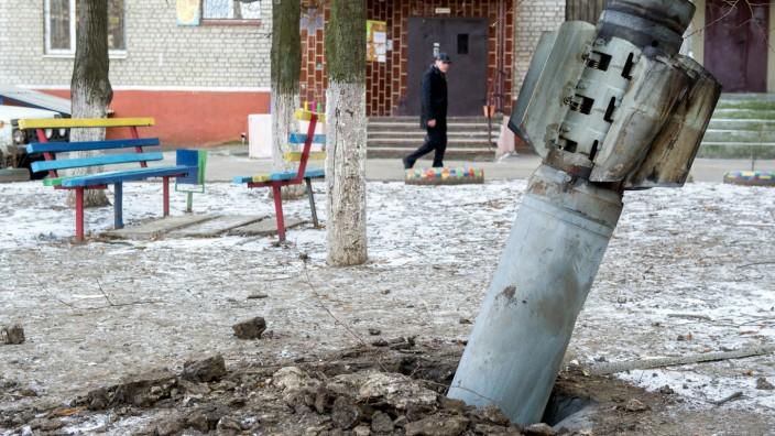 A man walks past an unexploded rocket in in the eastern Ukrainian city of Kramatorsk, in the Donetsk region, on February 11, 2015.