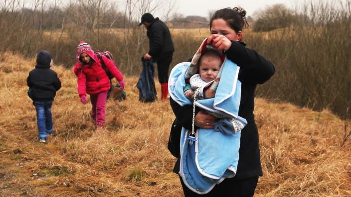 Eine Frau mit ihrem Baby nach dem illegalen Grenzübergang zwischen Ungarn und Serbien.