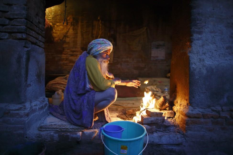 Hindu holy man, or sadhu, sits beside a fire at his ashram on the premises of Pashupatinath Temple in Kathmandu