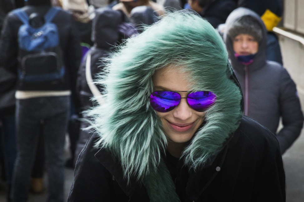 A model protects herself from cold wind as she leaves a presentation of the Victoria Beckham Fall/Winter 2015 collection during New York Fashion Week