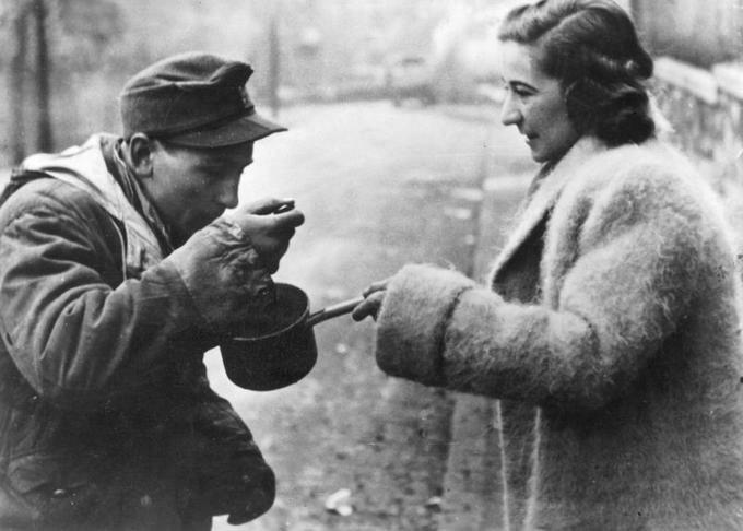Ungarin gibt einem deutschen Soldaten in Budapest zu essen, 1945; Bildstrecke Ostfront 1945