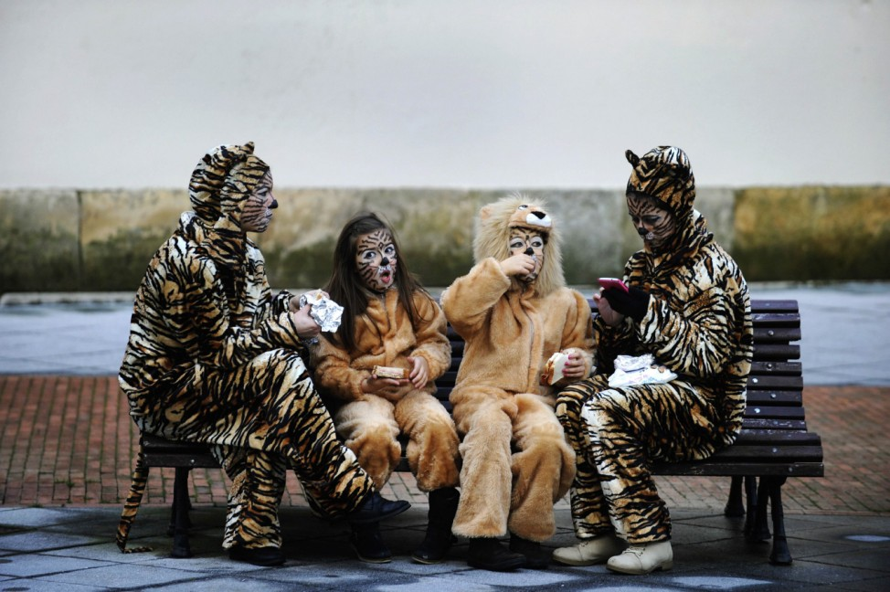 Two mothers and their children eat before participating in the parade of the Carnival in Gijon