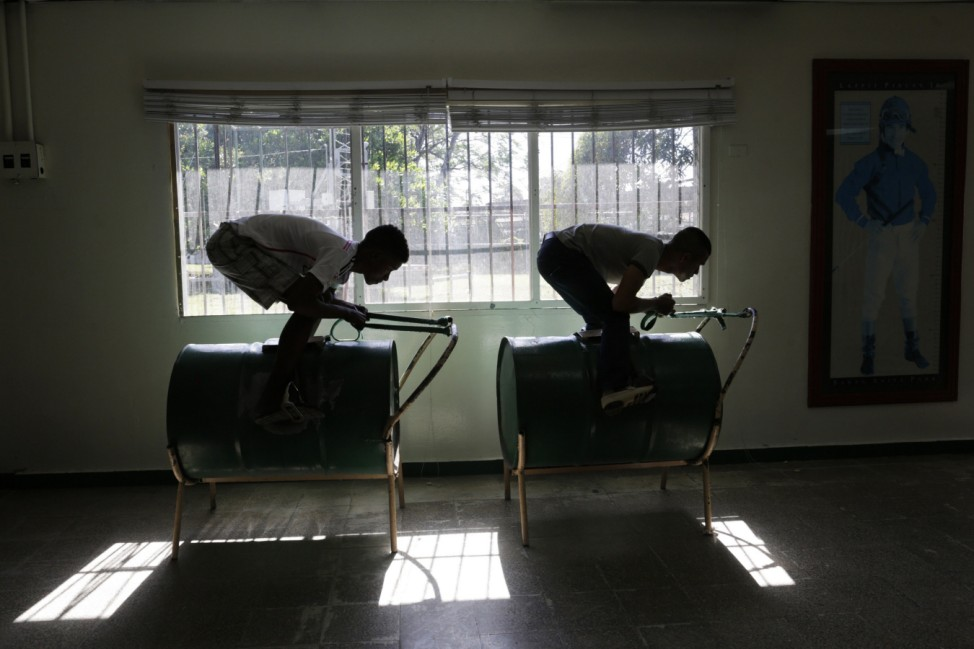 Jockey students practice their racing position on a horse simulator made from an oil barrel, known as 'Pangal', at The Jockeys School in Panama City
