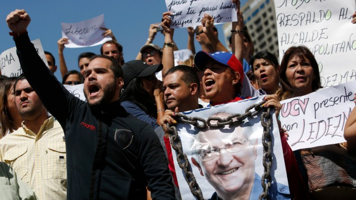 A supporter of Caracas Mayor Antonio Ledezma holds a poster of him with chains during a protest demanding his release in Caracas, Venezuela, Friday, Feb. 20, 2015. Demonstrators are condemning last ni